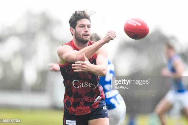 Tomas Bugg of the Casey Demons handballs the ball during the VFL round 14 game between the Casey Demons and North Melbourne at Casey Fields in...