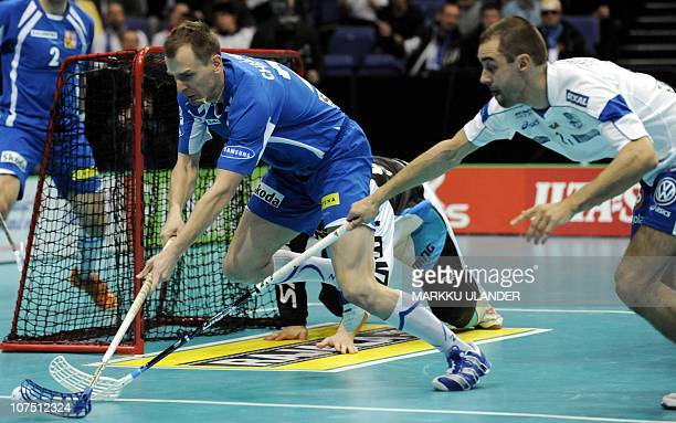 Tomas Chrapek of Czech Republic vies the ball with Finland's Rickie Hyvärinen during the World Floorball Championship 2010 semifinal game between...