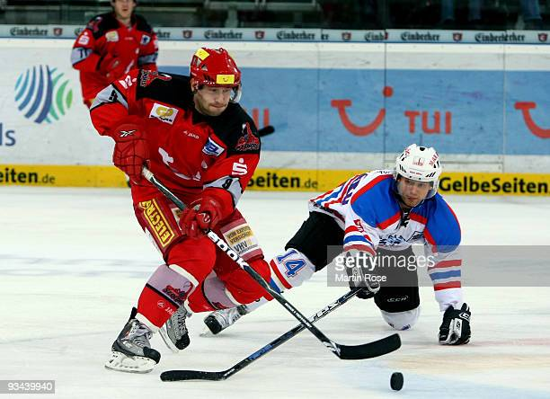 Tomas Dolak of Hannover and Tyler Mosienko of Nuernberg battle for the puck during the DEL match between Hannover Scorpions and Thomas Sabo Ice...