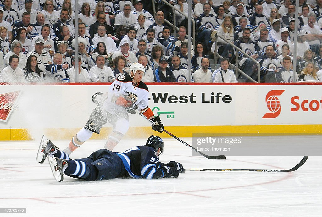 Tomas Fleischmann #14 of the Anaheim Ducks plays the puck as Tyler Myers #57 of the Winnipeg Jets slides to block the shot during third period action in Game Four of the Western Conference Quarterfinals during the 2015 NHL Stanley Cup Playoffs on April 22, 2015 at the MTS Centre in Winnipeg, Manitoba, Canada.