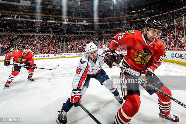Tomas Fleischmann of the Chicago Blackhawks and Nate Schmidt of the Washington Capitals chase after the puck during the NHL game at the United Center...