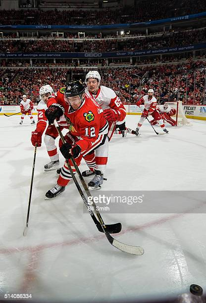 Tomas Fleischmann of the Chicago Blackhawks chases the puck against Andreas Athanasiou and Danny DeKeyser of the Detroit Red Wings in the third...