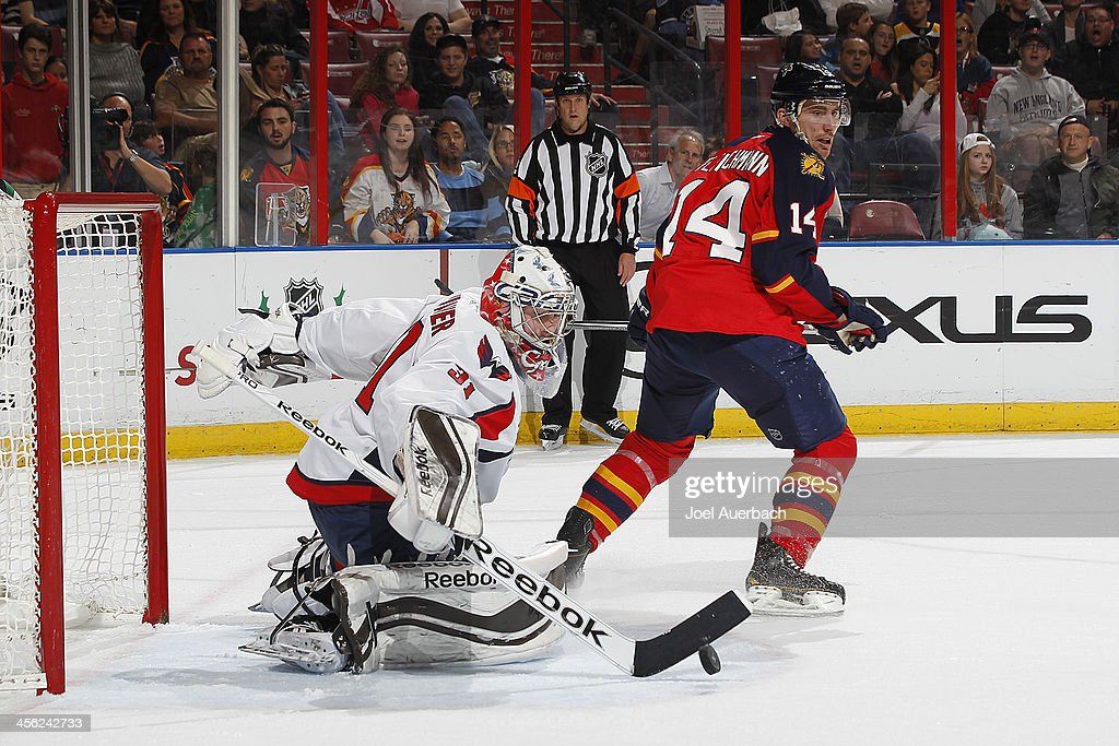 Tomas Fleischmann #14 of the Florida Panthers looks back as Goaltender Phillip Grubauer #31 of the Washington Capitals stops the shot at the BB&T Center on December 13, 2013 in Sunrise, Florida. The Panthers defeated the Capitals 3-2 in a shootout.