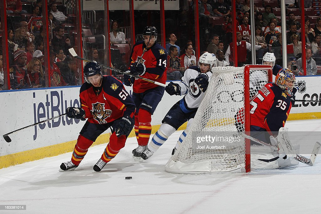 Tomas Fleischmann #14 of the Florida Panthers nudges Jim Slater #19 of the Winnipeg Jets into the back of the net as Brian Campbell #51 comes away with the puck at the BB&T Center on March 8, 2013 in Sunrise, Florida.