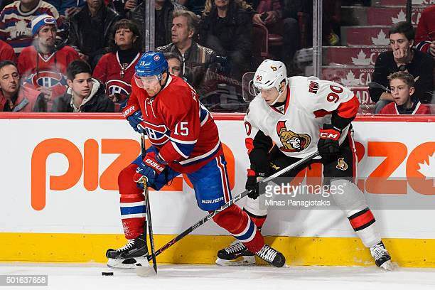 Tomas Fleischmann of the Montreal Canadiens and Alex Chiasson of the Ottawa Senators battle for the puck near the boards during the NHL game at the...
