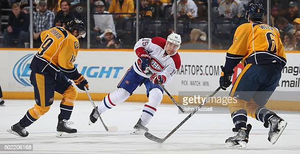 Tomas Fleischmann of the Montreal Canadiens passes the puck between Calle Jarnkrok and Shea Weber of the Nashville Predators during an NHL game at...