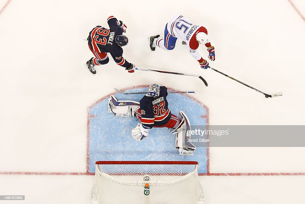 Tomas Fleischmann #15 of the Montreal Canadiens sakes with the puck against Antti Raanta #32 and Keith Yandle #93 of the New York Rangers at Madison Square Garden on November 25, 2015 in New York City.