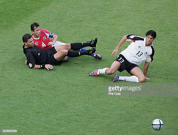Tomas Galasek of the Czech Republic and Michael Ballack of Germany collide with Tere Hauge the Referee during the UEFA Euro 2004 Group D match...