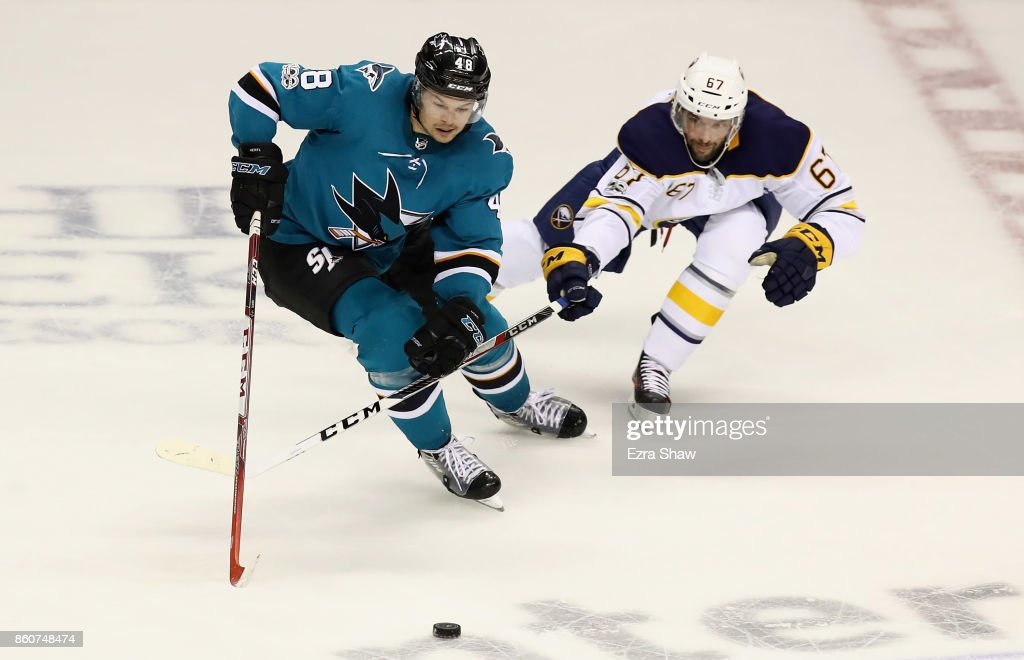 Tomas Hertl #48 of the San Jose Sharks and Benoit Pouliot #67 of the Buffalo Sabres go for the puck at SAP Center on October 12, 2017 in San Jose, California.