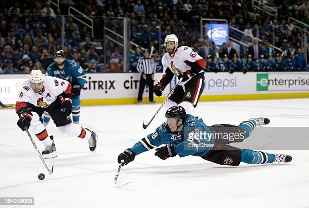 Tomas Hertl of the San Jose Sharks and Chris Phillips of the Ottawa Senators go for the puck at SAP Center on October 12 2013 in San Jose California
