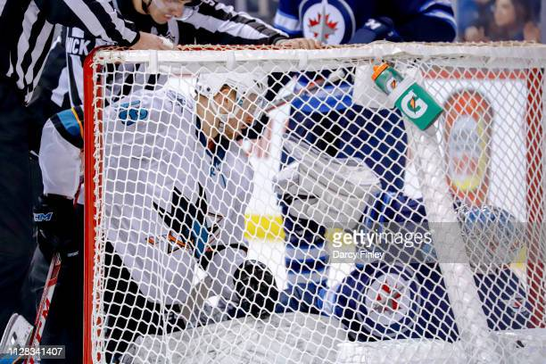 Tomas Hertl of the San Jose Sharks and goaltender Connor Hellebuyck of the Winnipeg Jets get themselves untangled from the net following a collision...
