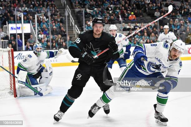 Tomas Hertl of the San Jose Sharks battles for the puck against Christopher Tanev of the Vancouver Canucks at SAP Center on November 23, 2018 in San...