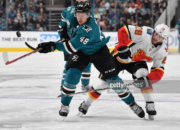 Tomas Hertl of the San Jose Sharks fights for the puck with Elias Lindholm of the Calgary Flames at SAP Center on November 11 2018 in San Jose...