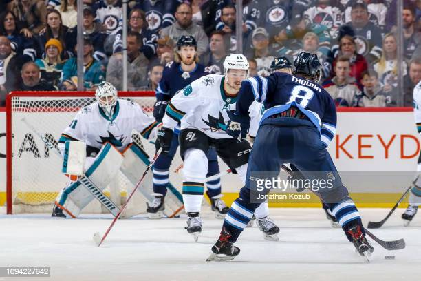 Tomas Hertl of the San Jose Sharks keeps an eye on Jacob Trouba of the Winnipeg Jets as he plays the puck at the point during third period action at...