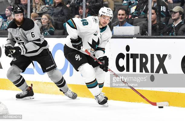 Tomas Hertl of the San Jose Sharks keeps the puck away from Jake Muzzin of the Los Angeles Kings at SAP Center on December 22 2018 in San Jose...
