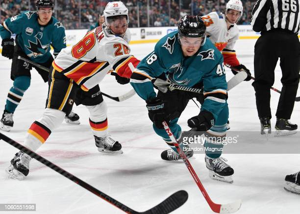Tomas Hertl of the San Jose Sharks reaches for the puck against Elias Lindholm of the Calgary Flames at SAP Center on November 11 2018 in San Jose...