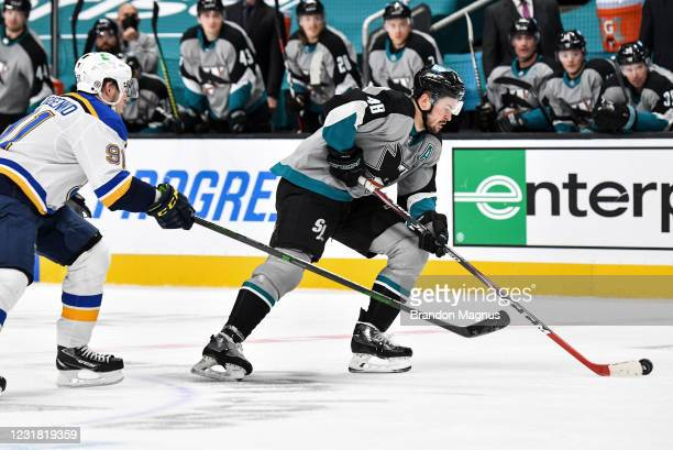 Tomas Hertl of the San Jose Sharks skates ahead with the puck against Vladimir Tarasenko of the St. Louis Blues at SAP Center on March 19, 2021 in...