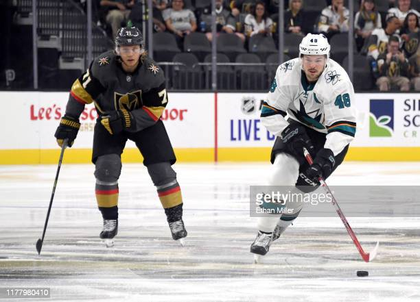 Tomas Hertl of the San Jose Sharks skates with the puck ahead of William Karlsson of the Vegas Golden Knights in the third period of their preseason...