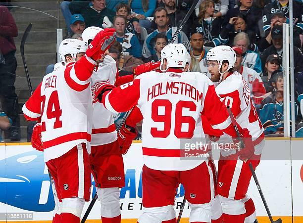 Tomas Holmstrom, Henrik Zetterberg, and Ruslan Salei of the Detroit Red Wings celebrate a third period goal against the San Jose Sharks in Game Five...