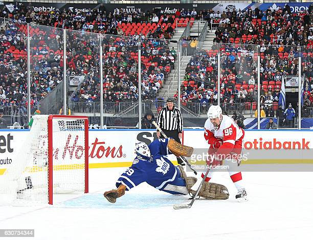 Tomas Holmstrom of the Detroit Red Wings Alumni is stopped by Mike Palmateer of the Toronto Maple Leafs Alumni during the 2017 Rogers NHL Centennial...