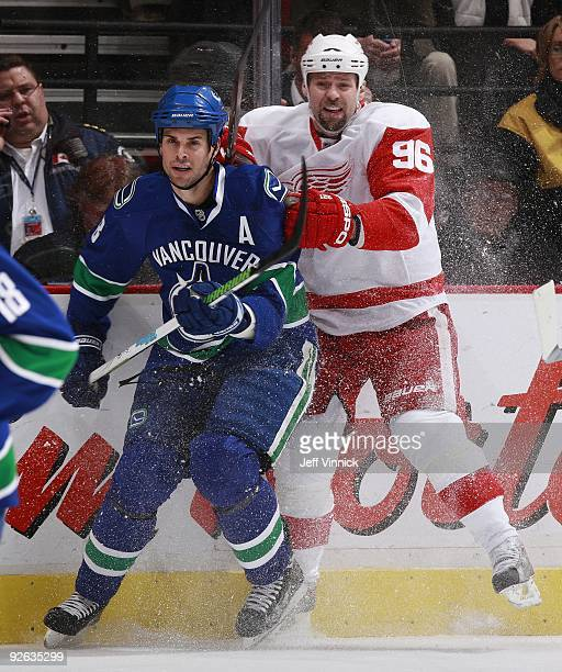 Tomas Holmstrom of the Detroit Red Wings and Willie Mitchell of the Vancouver Canucks battle along the boards during their game at General Motors...