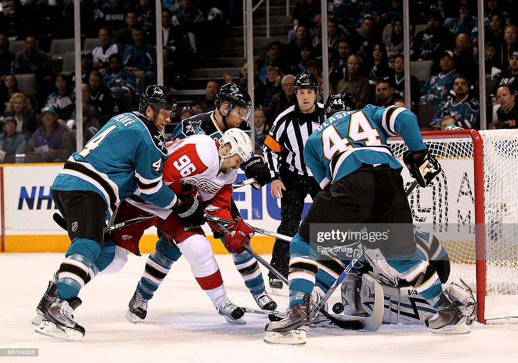 Tomas Holmstrom #96 of the Detroit Red Wings is surrounded by Shark defenders and goalie Evgeni Nabokov #20 of the San Jose Sharks in Game One of the Western Conference Semifinals during the 2010 NHL Stanley Cup Playoffs at HP Pavilion on April 29, 2010 in San Jose, California.