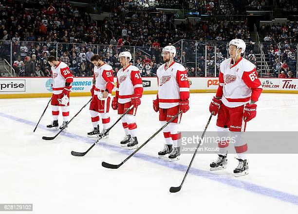 Tomas Jurco Frans Nielsen Luke Glendening Mike Green and Danny DeKeyser of the Detroit Red Wings stand on the ice during the singing of the National...