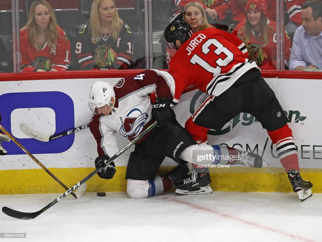 Tomas Jurco #13 of the Chicago Blackhawks and Tyson Barrie #4 of the Colorado Avalanche battle along the boards at the United Center on March 20, 2018 in Chicago, Illinois. The Avalanche defeated the Blackhawks 5-1.