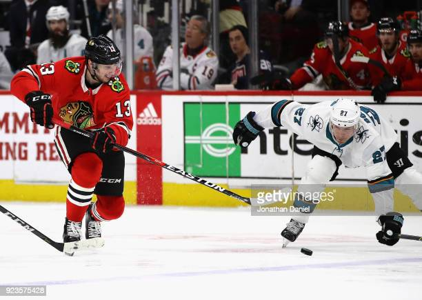 Tomas Jurco of the Chicago Blackhawks passes around Joonas Donskoi of the San Jose Sharks at the United Center on February 23 2018 in Chicago Illinois