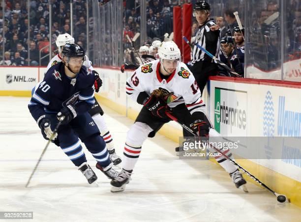 Tomas Jurco of the Chicago Blackhawks plays the puck as Joel Armia of the Winnipeg Jets gives chase during first period action at the Bell MTS Place...