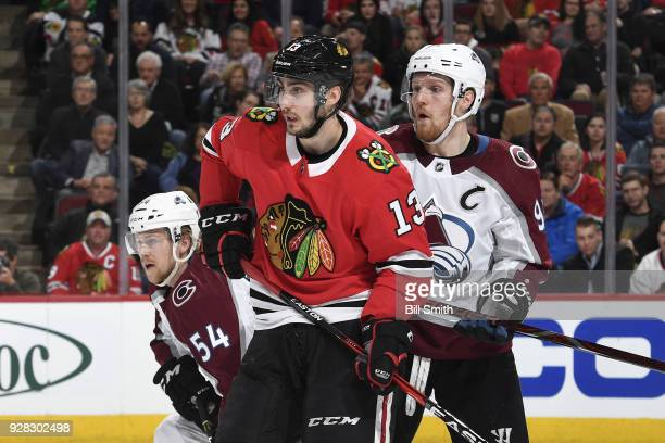 Tomas Jurco of the Chicago Blackhawks watches for the puck against Anton Lindholm and Gabriel Landeskog of the Colorado Avalanche in the first period...