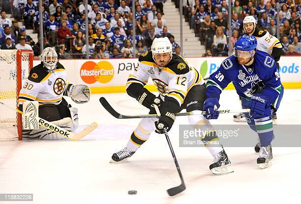 Tomas Kaberle of the Boston Bruins and Jannik Hansen of the Vancouver Canucks battle for the puck in front of Tim Thomas during second period of Game...