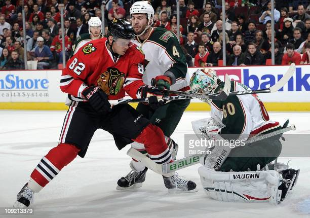Tomas Kopecky of the Chicago Blackhawks watches as goalie Jose Theodore of the Minnesota Wild stops the puck and Clayton Stoner of the Wild skates in...