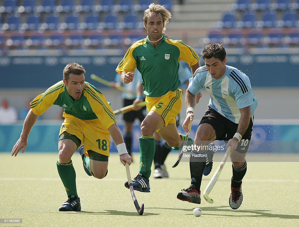 Tomas MacCormik #10 of Argentina and Wayne Denne #18 of South Africa run for the ball in the men's field hockey preliminaries on August 15, 2004 during the Athens 2004 Summer Olympic Games at the Helliniko Olympic Complex Hockey Centre in Athens, Greece. South Africa defeated Argentina 2-1.