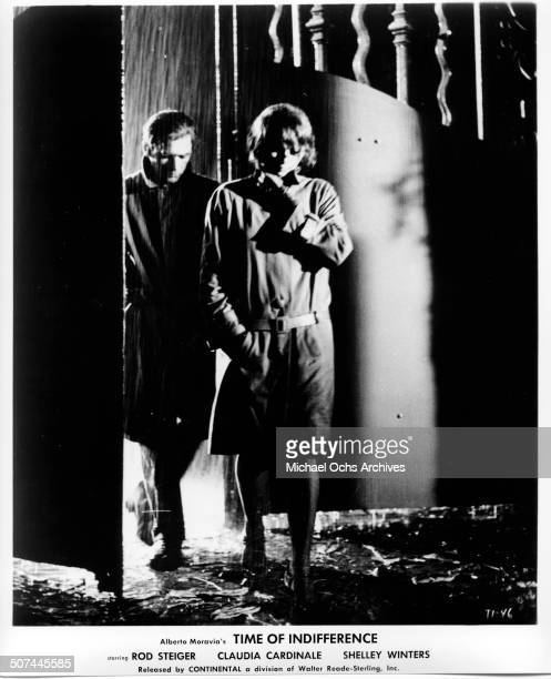 Tomas Milian and Claudia Cardinale walk in the rain in a scene from the movie 'Time of Indifference' circa 1964