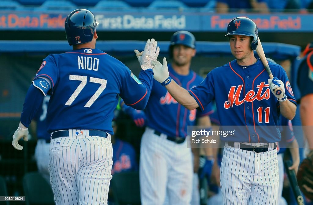 Tomas Nido #77 of the New York Mets high fives Ty Kelly #11 after hitting a home run during the seventh inning against the Houston Astros of a spring training game at First Data Field on March 6, 2018 in Port St. Lucie, Florida. The Mets defeated the Astros 9-5.
