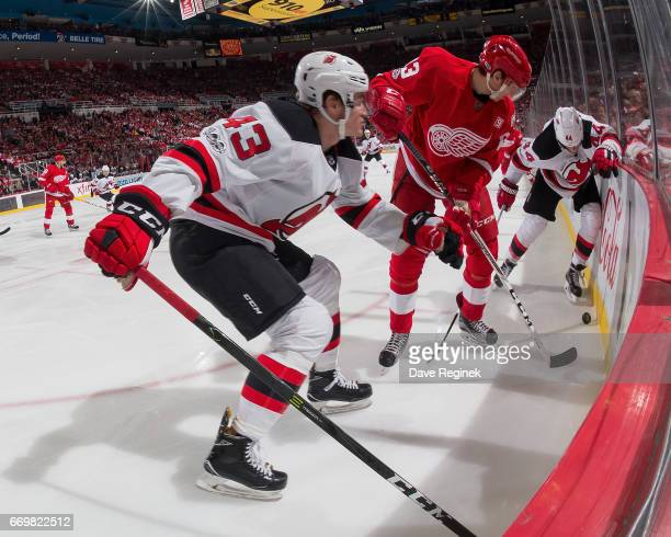 Tomas Nosek of the Detroit Red Wings battles along the boards with Ben Thomson and Miles Wood of the New Jersey Devils during the final home game...