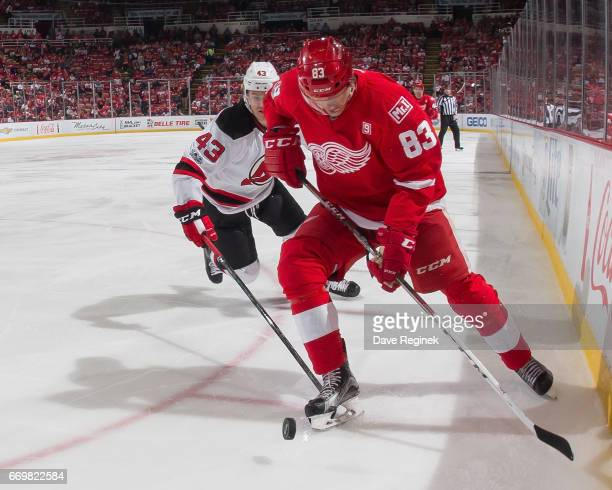 Tomas Nosek of the Detroit Red Wings controls the puck in front of Ben Thomson of the New Jersey Devils during the final home game ever played at Joe...