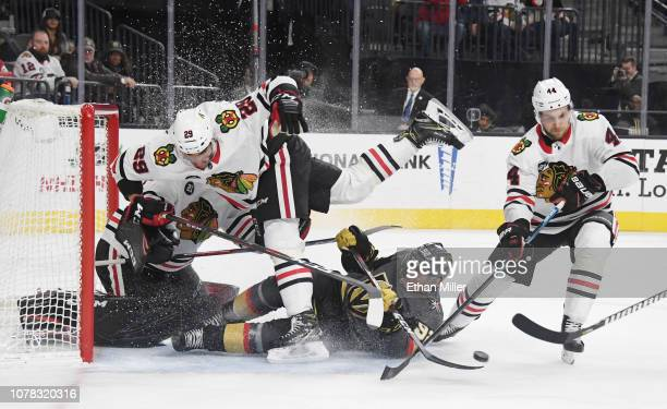 Tomas Nosek of the Vegas Golden Knights slides into Andreas Martinsen and goaltender Corey Crawford of the Chicago Blackhawks as Jan Rutta of the...