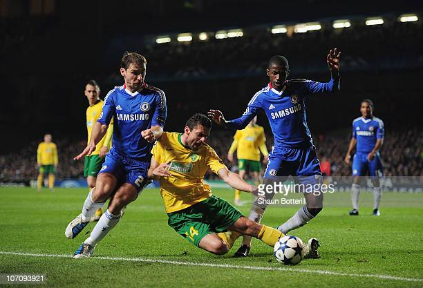 Tomas Oravec of MSK Zilina goes to ground under a challenge from Branislav Ivanovic and Ramires of Chelsea during the UEFA Champions League Group F...
