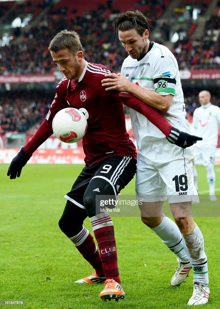 Tomas Pekhart (L) of Nuernberg is challenged by Christian Schulz of Hannover during the Bundesliga match between 1. FC Nuernberg and Hannover 96 at Grundig-Stadion on February 17, 2013 in Nuremberg, Germany.