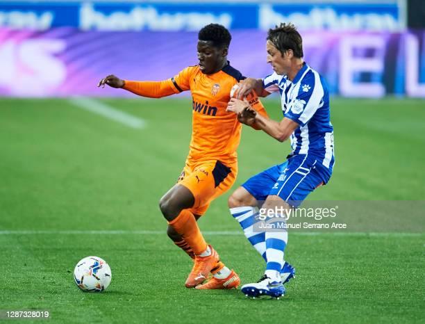 Tomas Pina of Deportivo Alaves duels for the ball with Yunus Dimoara Musah of Valencia CF during the LaLiga Santander match between Alaves and...