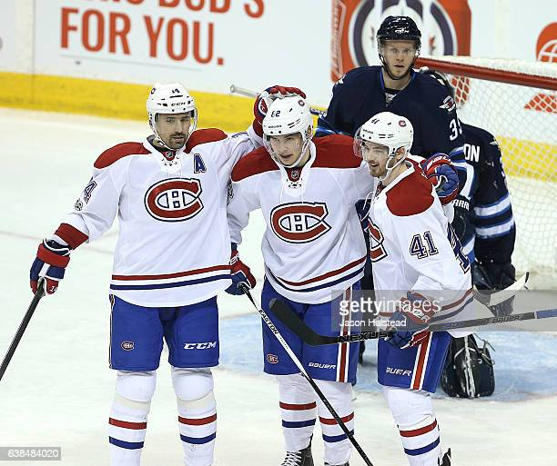 Tomas Plekanec and Paul Byron of the Montreal Canadiens congratulate Artturi Lehkonen as Toby Enstrom of the Winnipeg Jets looks on during NHL action...