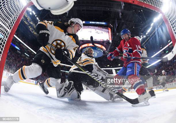 Tomas Plekanec of the Montreal Canadiens attempts to deflect the puck against Torey Krug and Tuukka Rask of the Boston Bruins in the NHL game at the...