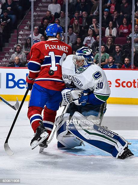 Tomas Plekanec of the Montreal Canadiens bumps into goaltender Ryan Miller of the Vancouver Canucks as he makes a save during the NHL game at the...