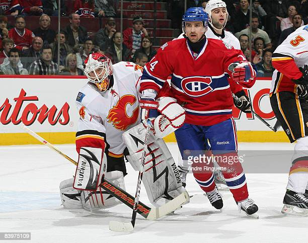 Tomas Plekanec of the Montreal Canadiens bumps Miikka Kiprusoff of the Calgary Flames outside the crease at the Bell Centre on December 9 2008 in...