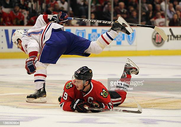 Tomas Plekanec of the Montreal Canadiens hops over Jonathan Toews of the Chicago Blackhawks at the United Center on December 21 2011 in Chicago...