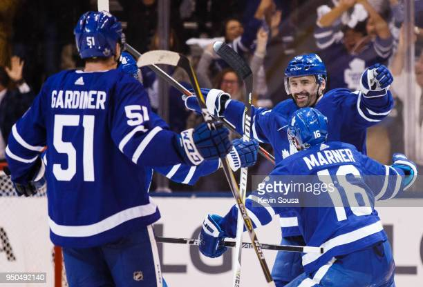 Tomas Plekanec of the Toronto Maple Leafs is congratulated on his empty net goal against the Boston Bruins by teammates Mitch Marner and Jake...