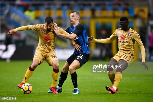 Tomas Rincon and MBaye Niang of Torino FC compete for the ball with Ivan Perisic of FC Internazionale during the Serie A football match between FC...