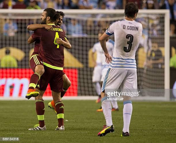 Tomas Rincon and Oswaldo Vizcarrondo of Venezuela embrace in front of Diego Godin of Uruguay during the 2016 Copa America Centenario Group C match at...